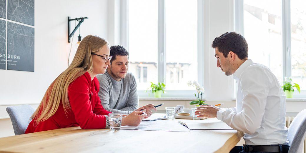 Zwei Männer und eine Frau sitzen am Tisch und besprechen Dokumente im Immobilienmaklerbüro