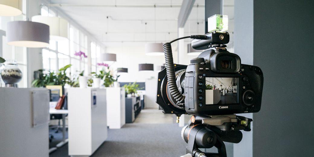 Spiegelreflexkamera mit eingeschaltetem Bildschirm auf einem stativ in ein offenes Büro gerichtet