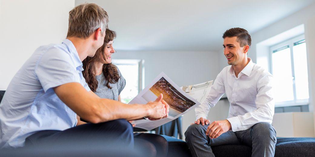 Immobilienmakler mit 2 Interessenten beim Gespräch in neuer Immobilie