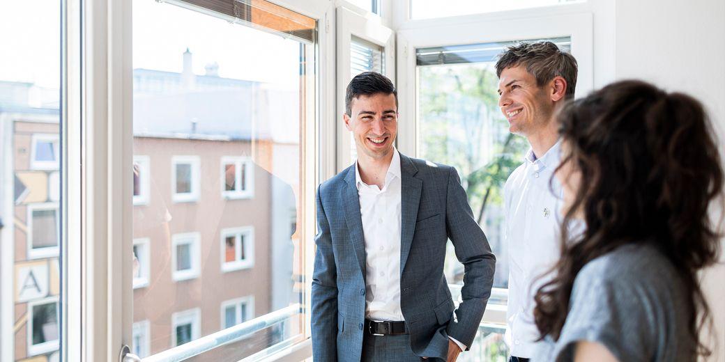 Immobilienmakler steht mit zwei Interessenten vor einer großen Fensterecke in einer Immobilie